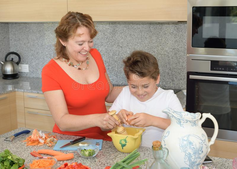 Mother and son preparing lunch using eggs and smile stock photography