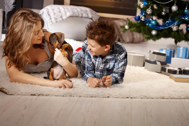 Mother and son with puppy at christmas. Young mother and son playing with puppy at christmas time, lying on floor royalty free stock images