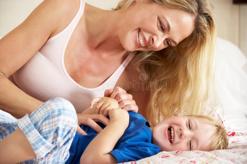 Mother And Son Relaxing Together In Bed Stock Photos