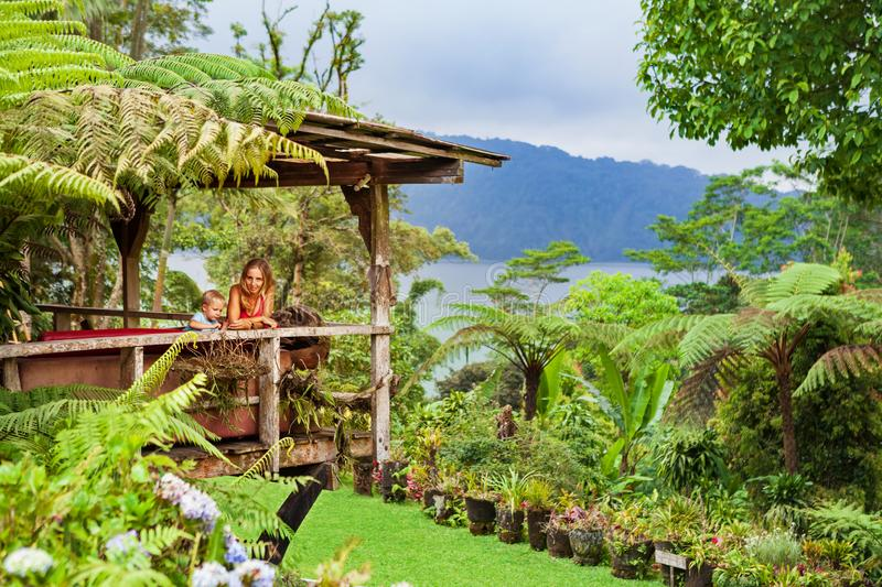 Mother, son relaxing on veranda with tropical garden view stock images