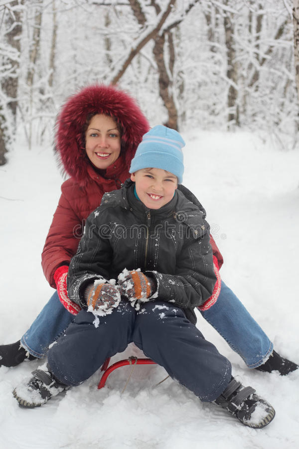 Mother, son ride on sled