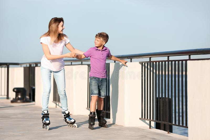 Mother and son roller skating on street royalty free stock images