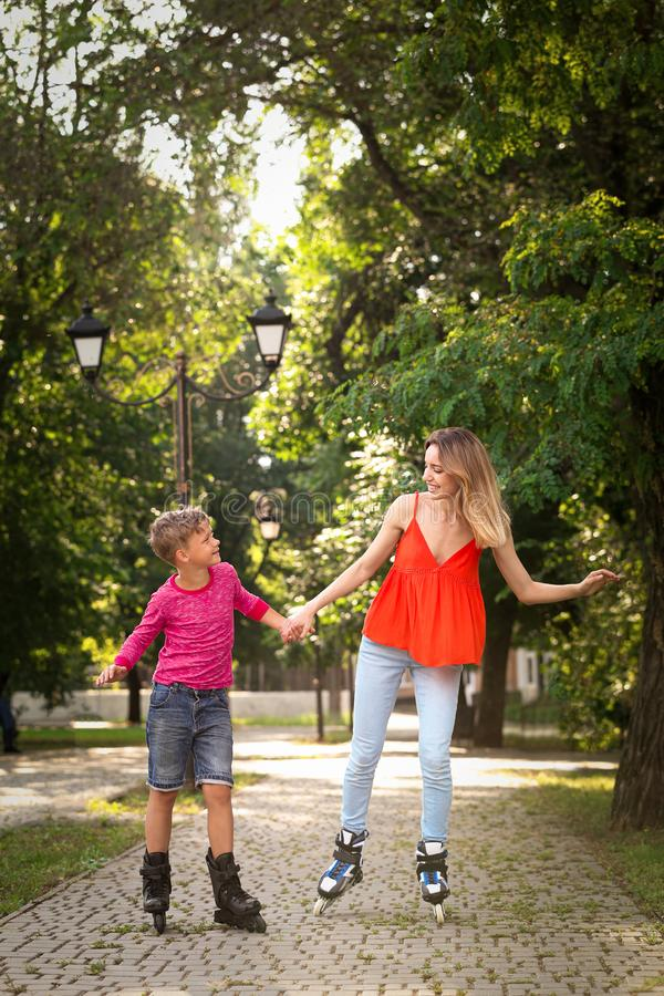 Mother and son roller skating in park stock photography
