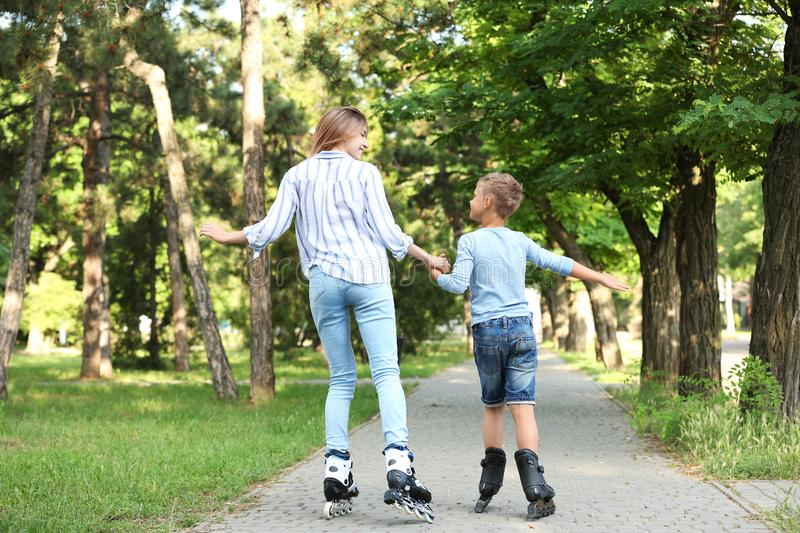 Mother and son roller skating in summer park royalty free stock photos