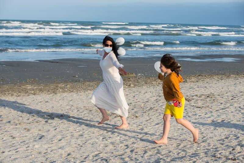 Mother and son running beach during Coronavirus stock photos