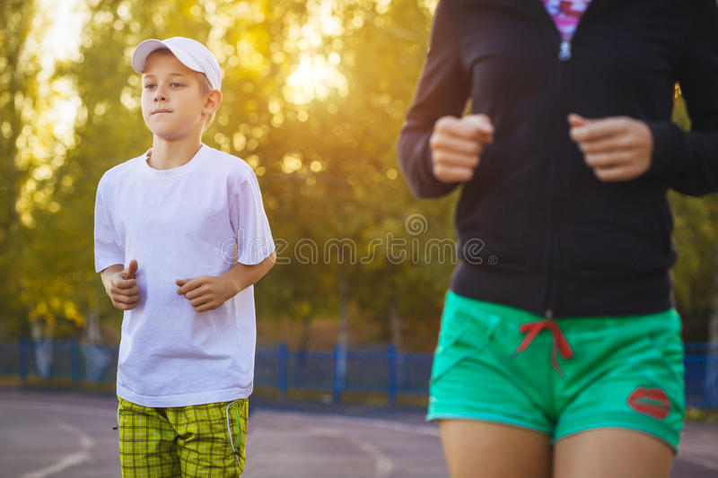 Mother and son are running or jogging for sport outdoors royalty free stock images