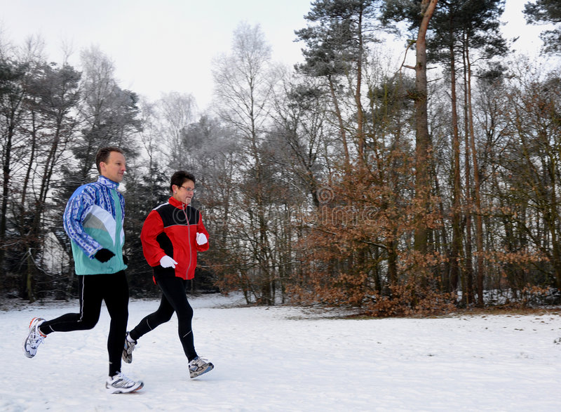 Mother and son running in wintertime stock images