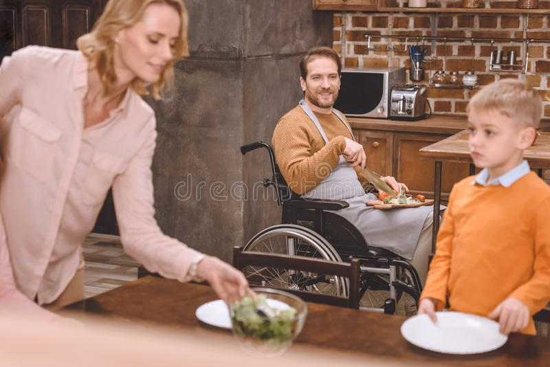 mother with son serving table for dinner while father in wheelchair cutting vegetables royalty free stock images