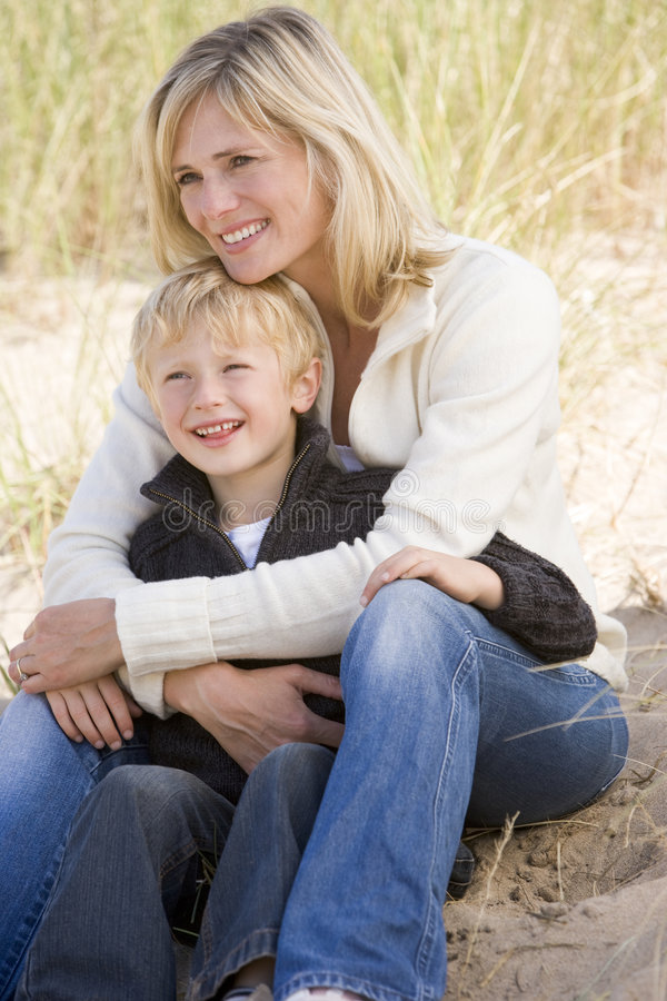 Mother and son sitting on beach smiling royalty free stock photos