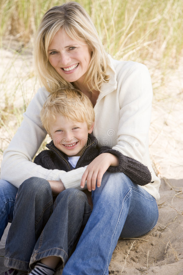 Mother and son sitting on beach smiling royalty free stock photography