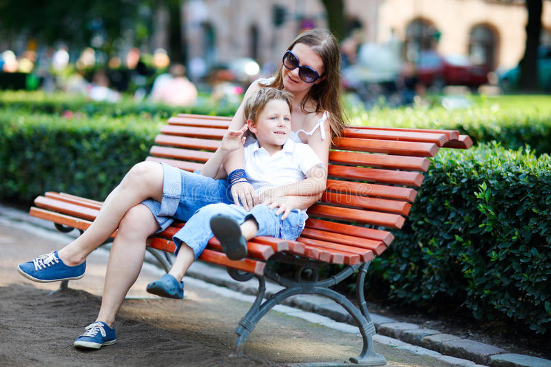 Mother and son sitting on bench in park royalty free stock images
