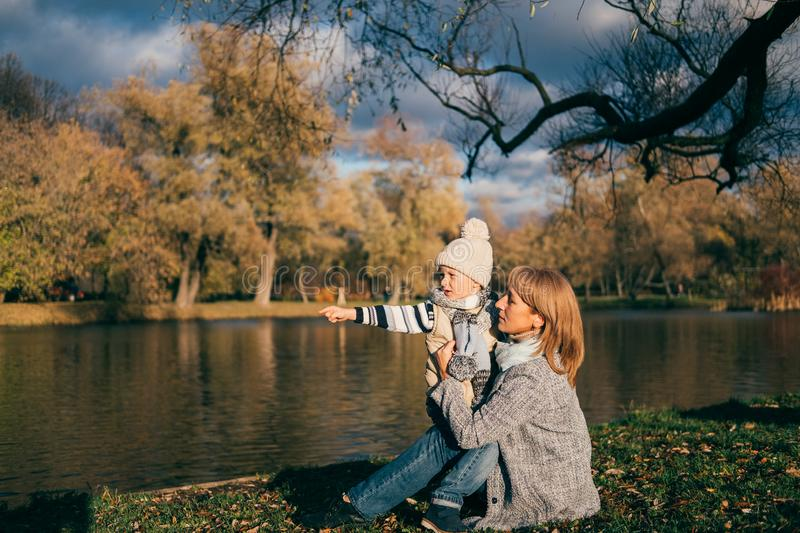 Mother and son sitting near lake in autumn park on sunset and looking away. Family having fun, hugging, laughing, relaxing, enjoy stock images