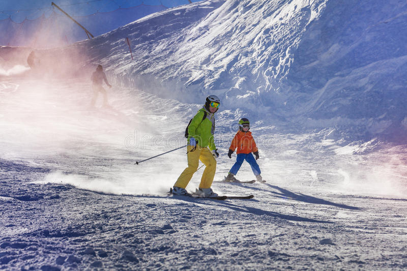 Mother and son ski down the mountain. Mom and child ski down the piste teaching how to go down with sunlight lit through snow mist royalty free stock photography
