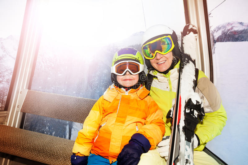 Mother and son in ski lift happy smile wear masks. Child and mother sit in cablecar lifting on top of the mountain with ski and smiling royalty free stock photo