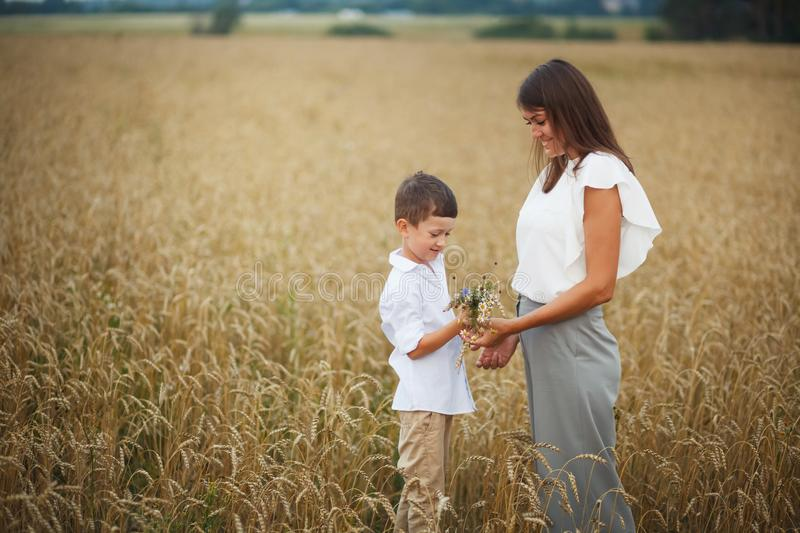 Mother with son smiling holding hands and embracing in a field in summer. The concept of maternal love and tenderness, the royalty free stock photography