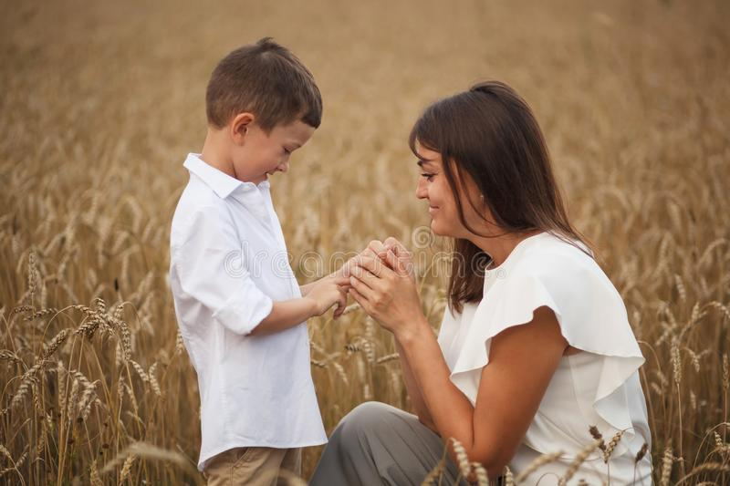 Mother with son smiling holding hands and embracing in a field in summer. The concept of maternal love and tenderness, the royalty free stock images
