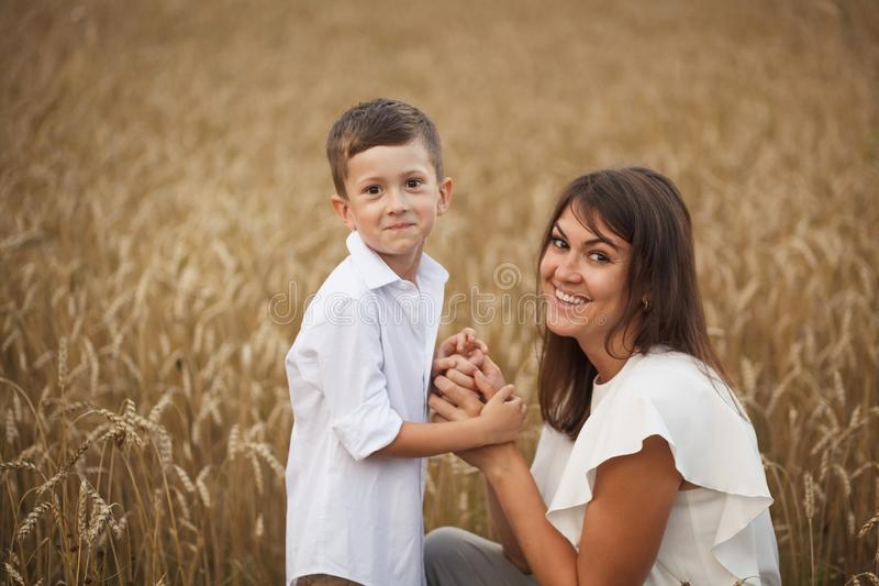 Mother with son smiling holding hands and embracing in a field in summer. The concept of maternal love and tenderness, the stock photography