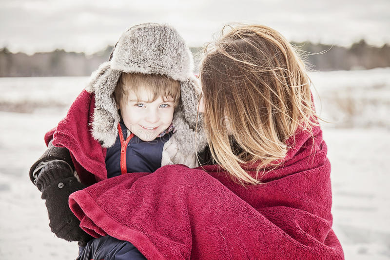 Mother and son snuggling under blanket. Outside in winter stock image