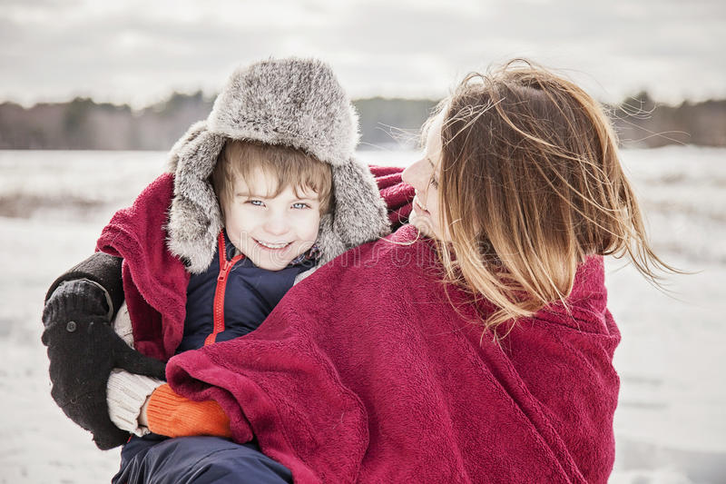 Mother and son snuggling under blanket. Outside in winter royalty free stock image
