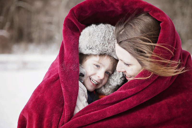 Mother and son snuggling under blanket. Outside in winter royalty free stock photography