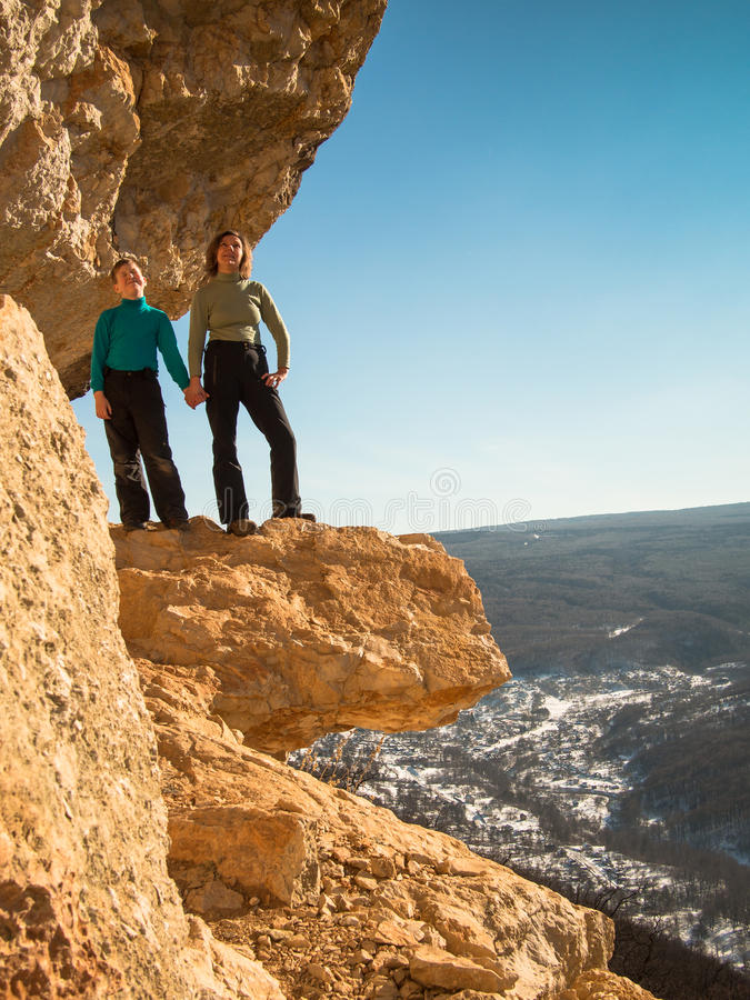 Mother and son standing at the cliff on the background of sky royalty free stock image