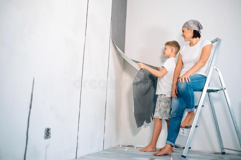 Mother and son take off wallpapers from wall and prepare room for renovation stock images