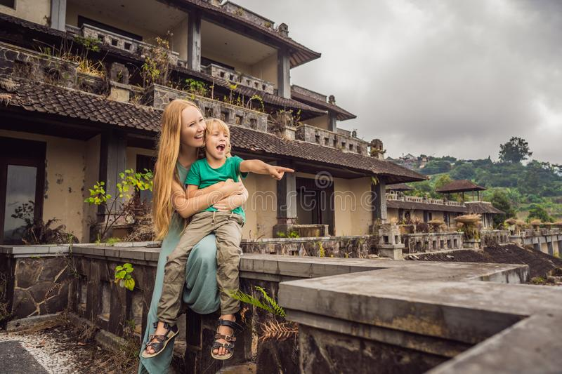 Mother and son tourists in abandoned and mysterious hotel in Bedugul. Indonesia, Bali Island. Bali Travel Concept.  royalty free stock image