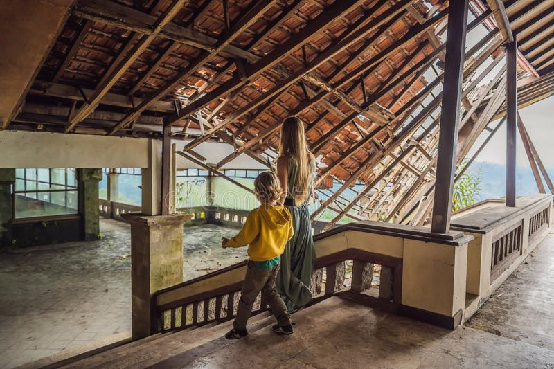 Mother and son tourists in abandoned and mysterious hotel in Bedugul. Indonesia, Bali Island. Bali Travel Concept stock images