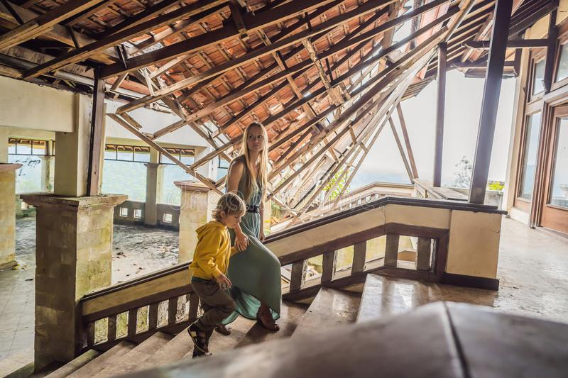 Mother and son tourists in abandoned and mysterious hotel in Bedugul. Indonesia, Bali Island. Bali Travel Concept.  stock photography