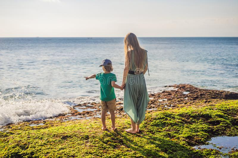 Mother and son tourists on Pantai Tegal Wangi Beach, Bali Island, Indonesia. Bali Travel Concept. Traveling with. Children concept. Kids friendly places stock image
