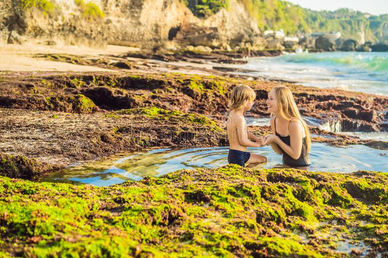 Mother and son tourists on Pantai Tegal Wangi Beach sitting in a bath of sea water, Bali Island, Indonesia. Bali Travel. Concept. Traveling with children stock photo