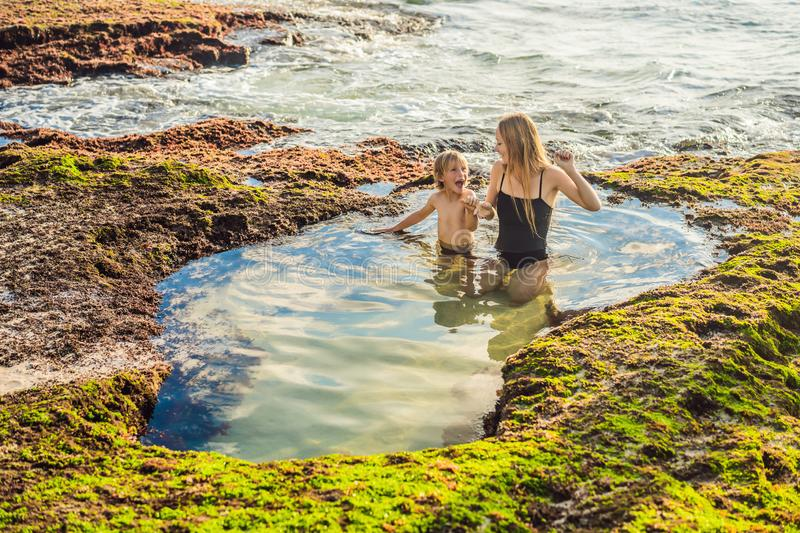 Mother and son tourists on Pantai Tegal Wangi Beach sitting in a bath of sea water, Bali Island, Indonesia. Bali Travel. Concept. Traveling with children royalty free stock images