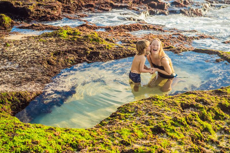 Mother and son tourists on Pantai Tegal Wangi Beach sitting in a bath of sea water, Bali Island, Indonesia. Bali Travel. Concept. Traveling with children royalty free stock photo