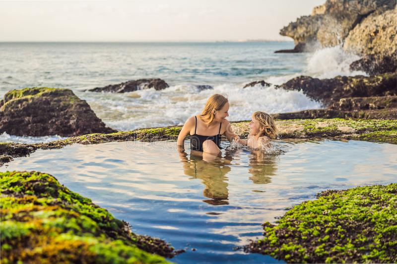 Mother and son tourists on Pantai Tegal Wangi Beach sitting in a bath of sea water, Bali Island, Indonesia. Bali Travel. Concept. Traveling with children stock photos
