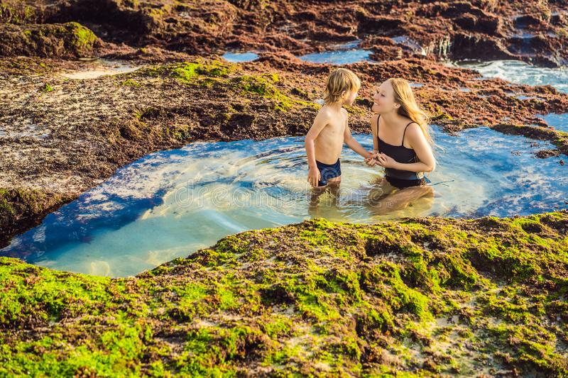 Mother and son tourists on Pantai Tegal Wangi Beach sitting in a bath of sea water, Bali Island, Indonesia. Bali Travel. Concept. Traveling with children royalty free stock photos