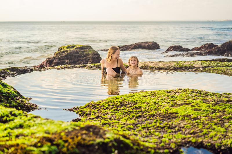 Mother and son tourists on Pantai Tegal Wangi Beach sitting in a bath of sea water, Bali Island, Indonesia. Bali Travel. Concept. Traveling with children stock photography