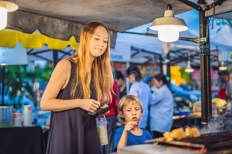 Mother and son are tourists on Walking street Asian food market royalty free stock photos