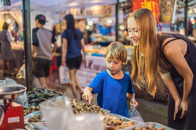Mother and son are tourists on Walking street Asian food market royalty free stock photo