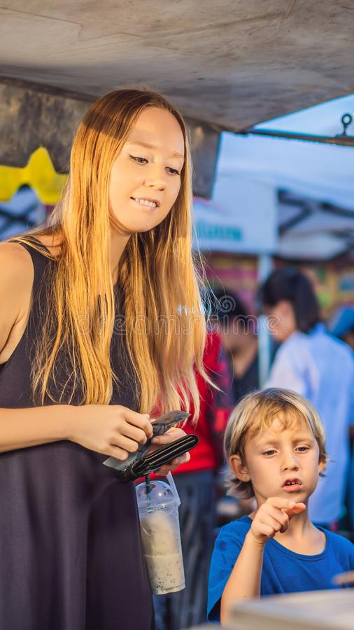 Mother and son are tourists on Walking street Asian food market VERTICAL FORMAT for Instagram mobile story or stories royalty free stock photography