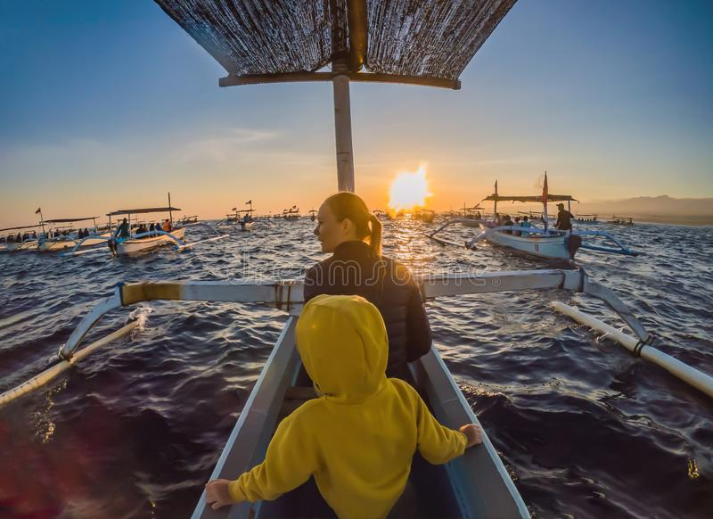 Mother and son travelers meets dawn in the sea on a boat.  stock photos