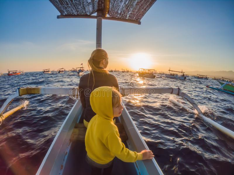 Mother and son travelers meets dawn in the sea on a boat.  royalty free stock image