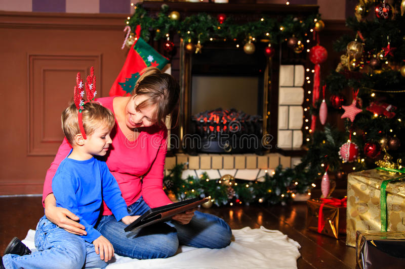 Mother and son using tablet pc by a fireplace stock photos