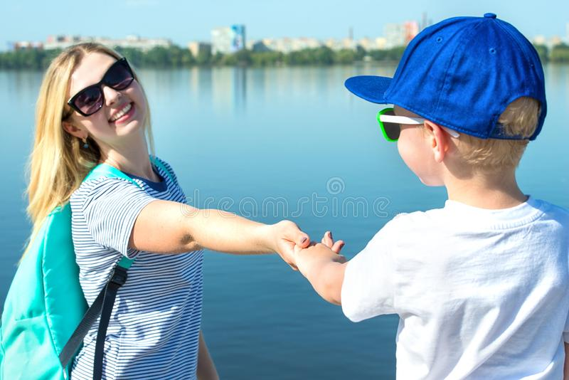 Mother and son walk along the promenade and hold hands. stock images