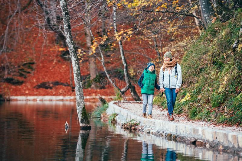 Mother and son walk in beautiful autumn park near lake royalty free stock photo