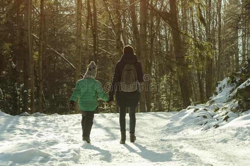 Mother with son walking along snow-covered road against the background of coniferous forest. Winter sunny day royalty free stock image