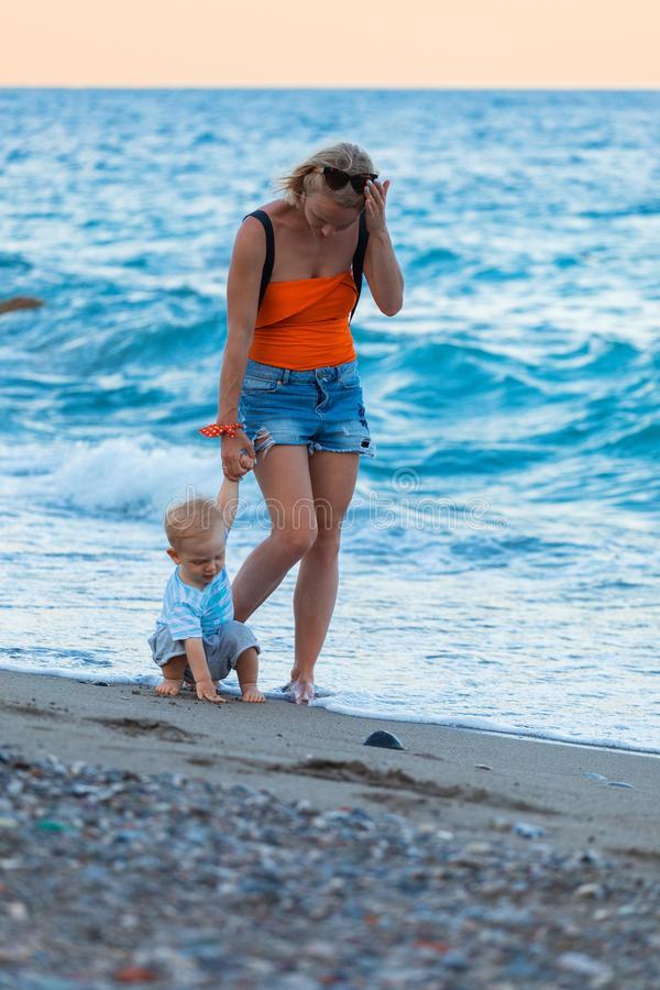 Mother and son walking on sunset beach royalty free stock image