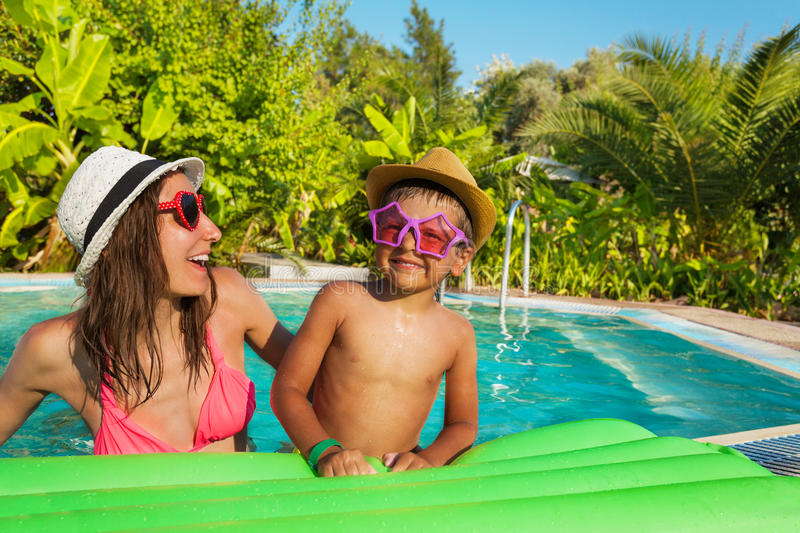 Mother and son wearing sunglasses lay on mattress. Happy mother and son wearing sunglasses and hats on mattress in the swimming pool outside in summer stock image