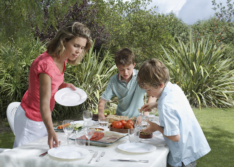 Mother And Sons Setting Dinner Table Outdoors royalty free stock photos