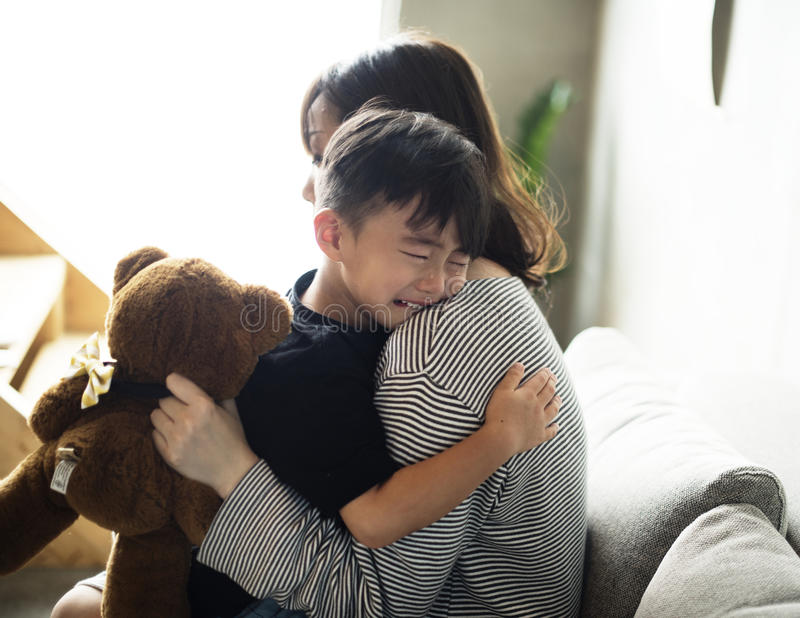 Mother sooth her son from sadness stock image