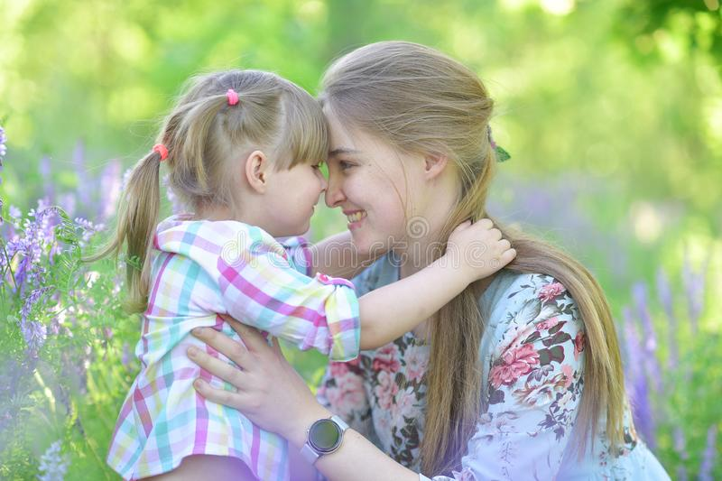 Mother speaks to baby girl daughter, plays, grimacing, laughing stock photos